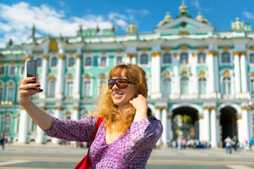 Selfie of a young female tourist near the Winter Palace