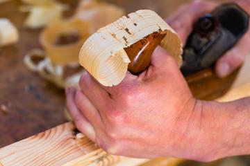 Tischler oder Schreiner mit Hobel in Tischlerei