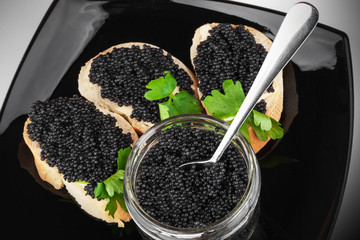 Sandwiches with black caviar on dark plate