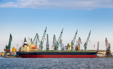 Loading with cranes of big industrial cargo ship in Varna port