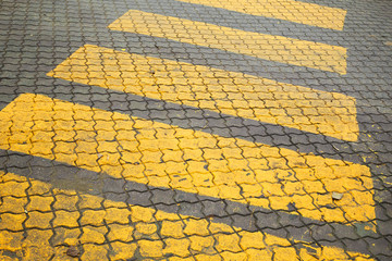 Pedestrian crossing, yellow marking on cobblestone road pavement