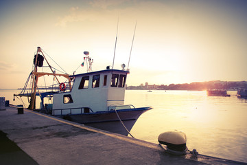 Industrial fishing boat is moored in port. Vintage toned photo