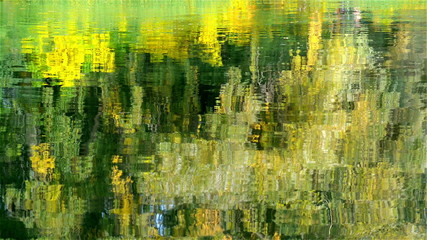 Autumn. Yellow foliage of trees is reflected in lake water.