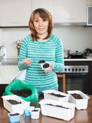 girl in green making soil for seedlings