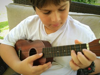 boy playing ukulele
