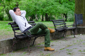 Young man sitting on the bench in the park