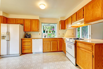 Kitchen room with maple cabinets and white appliances