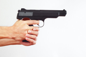Hands with semi-automatic handgun on a white background