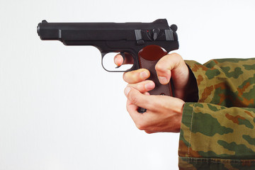 Hands in camouflage uniform with gun on a white background