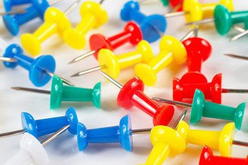 Multicolored office thumbtacks on white desktop close up