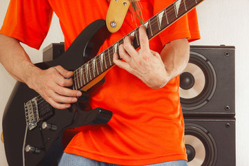 Hands of man playing the electric guitar closeup