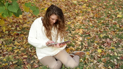 Smiling girl with tablet on the autumn landscape, outdoors