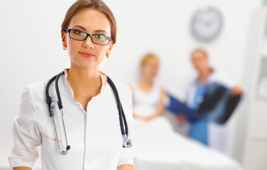 Woman doctor smiling and looking to the camera while a medical
