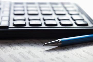 Calculator, pen, document lying on the desk