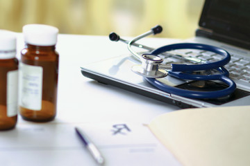 Laptop, stethoscope,bottle of pills, rx on the desk.