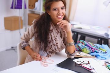 Smiling female fashion designer sitting at office desk