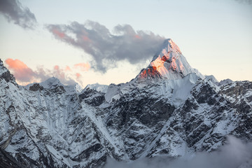 First rays of the rising sun on the top of Ama Dablam peak