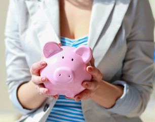 Young beautiful woman standing with piggy bank (money box), on