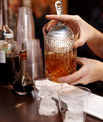 Bartender is straining cocktail into glass