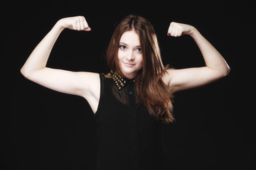 teen girl showing her muscles on black
