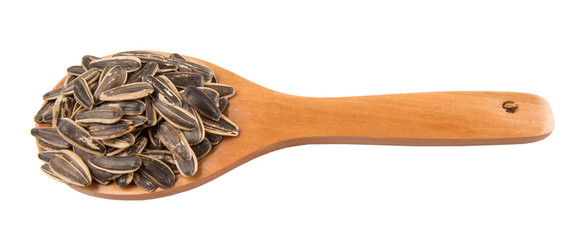 Sunflower seeds on wooden spoons over white background