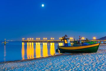 Baltic beach with fishing boat at night, Poland