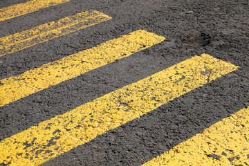 Pedestrian crossing road marking, yellow lines on gray asphalt