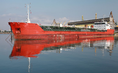 Red industrial cargo ship moored in port