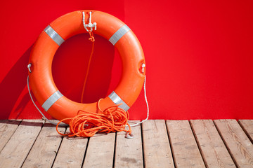 Lifebuoy stands on wooden floor nearby red wall of lifeguard sta