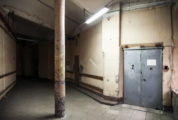 Empty dark industrial hall interior with metal elevator door