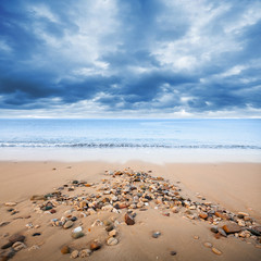 Atlantic ocean coast with wet small stones on the sand