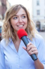Moderatorin mit blonden Locken bei der Arbeit