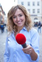 Journalistin mit blonden Locken befragt einen Passanten