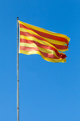 Flag of Catalonia waving on the wind above blue sky