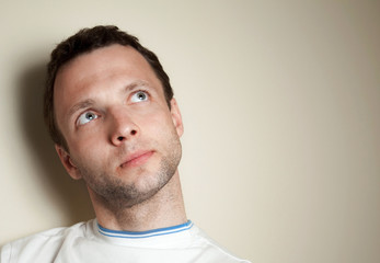Thinking young Caucasian man in white t-shirt. Closeup portrait