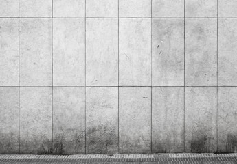 Empty urban interior with tiling on gray concrete wall and aspha