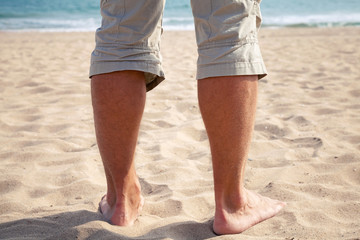 Legs of Young Caucasian man standing on sandy beach