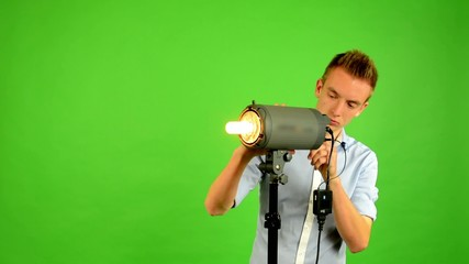 man - green screen - photographic studio - man works with light