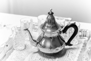 Metal Arabic teapot with glasses, black and white photo