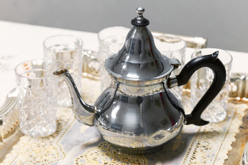 Arabic tea theme. Metal teapot with glasses on salver