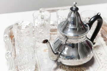Moroccan tea theme. Shining metal teapot with glasses
