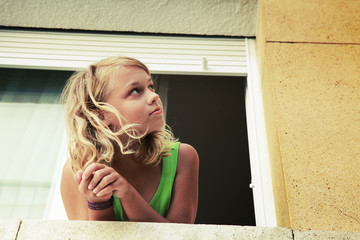 Little blond Caucasian girl in the window, outdoor vintage toned