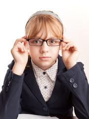 Little blond schoolgirl with glasses, closeup studio portrait