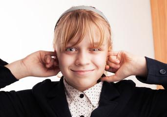 Blond smiling schoolgirl plugs fingers in his ears