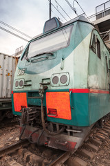 Modern green cargo train locomotive with red signs