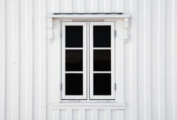 Window in white wooden wall. Norway architecture