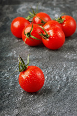 Red cherry tomatoes in water drops on the black granite surfaces