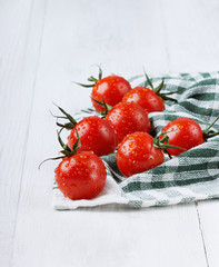 Red cherry tomatoes in water drops on a green linen napkin