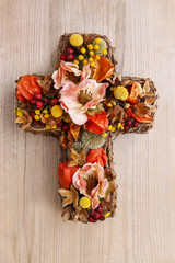 Cross made of artificial flowers and autumn plants.