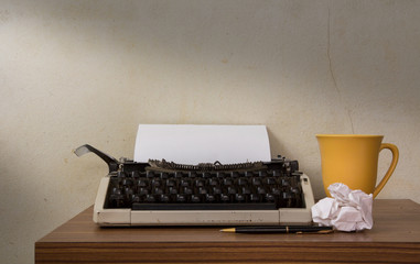 Typewriter with coffee cup and pen.